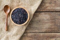 Riceberry orgânico na bacia de madeira com a colher de madeira no pano de saco do gunny na tabela de madeira Imagens de Stock Royalty Free