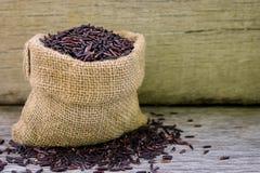 Riceberry ryż w konopie grabiją na drewnianym tle fotografia royalty free