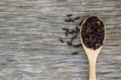 Riceberry w drewnianej łyżce na nieociosanym drewnianym tle zdjęcie royalty free