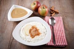 Ricepudding med kanel- och äpplesås Arkivfoto