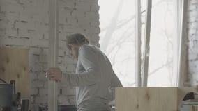 Ricerca del carpentiere qualcosa fra i materiali di falegnameria Tenga l'ostacolo del metallo in mani video d archivio