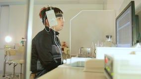 Ricerca della clinica di oftalmologia ragazza con gli elettrodi sulla testa che guarda al monitor - sistema diagnostico del ` s d video d archivio