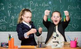 Ricerca di progetto della scuola Esperimento della scuola Uniforme scolastico delle ragazze eccitato provando la loro ipotesi Scu immagini stock