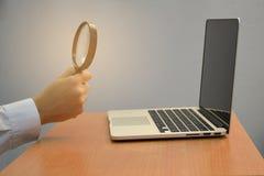 Ricerca maschio della lente d'ingrandimento della tenuta della mano di affari e computer portatile o computer per il concetto cre immagini stock libere da diritti