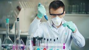 Ricercatore con il tubo ed il contagoccia nel laboratorio moderno stock footage