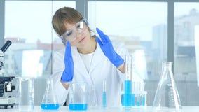 Ricercatore femminile che immagina nuova idea in laboratorio, creativo Fotografia Stock