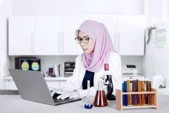 Ricercatore femminile che lavora con il computer portatile Fotografia Stock
