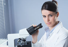 Ricercatore femminile che lavora con il microscopio Fotografie Stock
