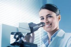 Ricercatore femminile che lavora con il microscopio Immagine Stock