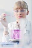 Ricercatore femminile che sostiene una provetta in laboratorio Immagine Stock