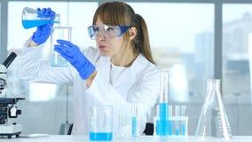 Ricercatore femminile Pouring Chemical in becher per reazione in laboratorio immagine stock libera da diritti