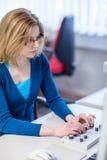 Ricercatore grazioso e femminile che utilizza un microscopio in un laboratorio Immagine Stock