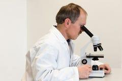 Ricercatore Looking Through Microscope Fotografia Stock Libera da Diritti
