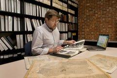 Ricercatore in mappe d'esame dell'archivio ed altro materiale archivistico Fotografia Stock Libera da Diritti
