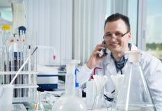 Ricercatore maschio che utilizza telefono cellulare nel suo luogo di lavoro nel laboratorio Immagini Stock