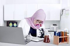 Ricercatore musulmano che lavora con il microscopio Immagini Stock