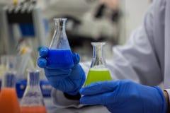 Ricercatore o scienziato o studente di phd che mescola che verde e blu Fotografie Stock