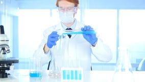 Ricercatore Pouring Chemical in becher per reazione in laboratorio, fotografia stock libera da diritti