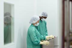 Ricercatori che controllano strumentazione nell'industria di Biotech Immagini Stock