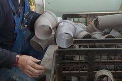 Ricerche sanitarie dell'installatore in una grande scatola per una curvatura adatta del collegamento per il tubo di acque reflue fotografia stock