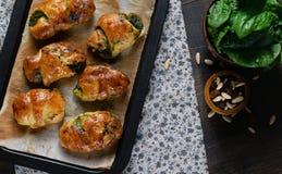 Ricetta casalinga dei croissant farciti con spinaci e la ricotta sulla carta di cottura nel piatto di cottura Fondo rustico scuro fotografia stock libera da diritti