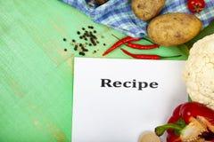 Ricetta culinaria, asciugamano, cucchiaio e varie verdure Immagine Stock