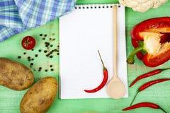 Ricetta culinaria, asciugamano, cucchiaio e varie verdure Immagini Stock