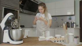Ricetta della lettura della casalinga sullo Smart Phone nella cucina archivi video