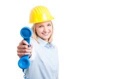 Ricevitore telefonico d'uso della tenuta del casco dell'architetto femminile Fotografie Stock