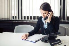 Ricezione della telefonata di cattive notizie Sguardo sconcertante controllando le note e lavoro di ufficio Responsabile che riso fotografia stock libera da diritti