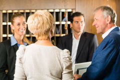 Ricezione - gli ospiti controllano un hotel Immagine Stock Libera da Diritti