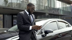 Rich Afro-American man waiting for partners near office building to do business. Stock photo royalty free stock photo