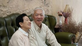 Rich Asian senior parents sit in luxury beautiful house background royalty free stock photo