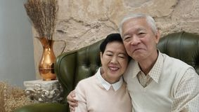 Rich Asian senior parents sit in luxury beautiful house background stock image