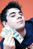 Rich Boy. A young man peers at the camera while holding several 10-dollar bills near his face Stock Photography