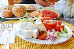 Rich breakfast. Rolls, fruits, cheese and vegetables in a rich and colorful breakfast Royalty Free Stock Photography