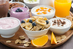 Rich breakfast buffet with cereals, yoghurt and fruit. On wooden tray, close-up royalty free stock photo