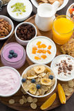 Rich breakfast buffet with cereals, yoghurt and fruit. On wooden tray, top view, vertical stock image