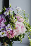 Rich bunch of pink peonies peony and lilac eustoma roses flowers in glass vase on white background. Rustic style, still Stock Photos