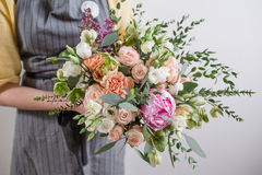 Rich bunch of pink peonies and white eustoma roses flowers, green leaf in glass vase. Fresh spring bouquet. Summer Royalty Free Stock Images