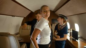 Rich business colleagues and air hostess dancing inside of aircraft first class stock video footage