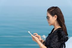 Rich business woman playing smart phone on luxury yacth. royalty free stock photos