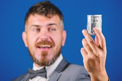 Rich businessman hold rolled money. Man bearded hipster hold rolled dollars banknotes. Guy formal suit offer bribe or. Purchase. Hipster offer money blue royalty free stock images