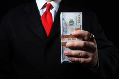 Rich businessman holding pack of money. Photo of a rich businessman in black siut with red tie holding a money pack Stock Images