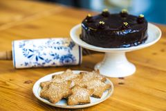 Rich chocolate cake and star shaped cookies Royalty Free Stock Image