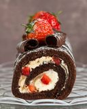 Rich Chocolate Swiss Roll. Decorated with strawberries on glass comport Stock Image
