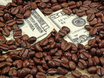 Rich Coffee. Currency buried in a heap of coffee beans, ala Rich Coffee concept Royalty Free Stock Photos