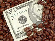 Rich Coffee. Currency buried in a heap of coffee beans, ala Rich Coffee concept Stock Photos