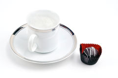 Rich coffee break. Afternoon indulgence: capucino coffee or latte served in fancy gold trim cup and saucer with chocolate Royalty Free Stock Images