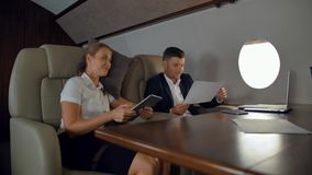 Rich colleagues discussing about business inside of luxury jet stock footage